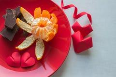 På den röda plattan är choklad, tangerin och två hjärtor som göras av Royaltyfri Foto