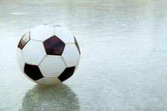 På den tunna isen är en fotboll som flög av fältet bollen på fryst royaltyfri foto