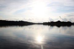 På den tysta sjön med solen och himlen Fotografering för Bildbyråer