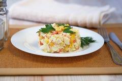 På den vita plattan klibbar en sallad av krabban royaltyfri bild