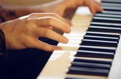 På det musikaliska tangentbordinstrumentet spelar en man en melodi med hans händer royaltyfria foton