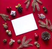På en bakgrund för rött hallon är det nya året och julpynt och prydliga guld- filialer ordnade i en cirkel och ett ark Arkivbilder