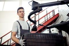 På en bilservice: en ung och attraktiv grabb kontrollerar ett gummihjul på arbete royaltyfri bild