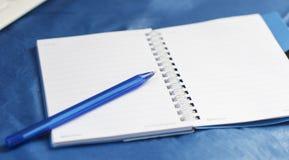 På en blå bakgrund - anteckningsbok- och blåttpennan Royaltyfria Bilder