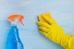 På en blå bakgrund gör en hand ren i en gul handske yttersidan med en svamp, bredvid en flaska med en sprej av rengörande flytand royaltyfria foton