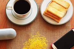 På en brun bakgrund finns det ett svart kaffe, ett knaprigt bröd och Royaltyfri Foto