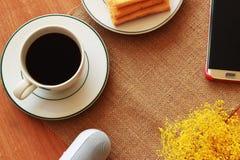 På en brun bakgrund finns det ett svart kaffe, ett knaprigt bröd och Arkivbilder
