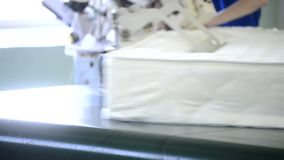 På en fabriksarbetare i maskin bearbetade kanten av madrassen lager videofilmer