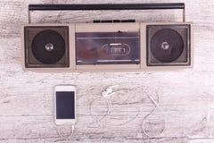 På en grå telefon och hörlurar för bakgrundskassettregistreringsapparat royaltyfria bilder
