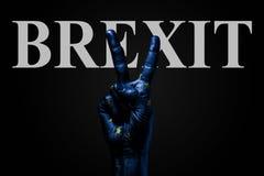 På en hand med en målad EU-flagga och inskriften BREXITE, på en mörk bakgrund visar ett fredtecken, ett symbol av fred, royaltyfri bild