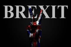 På en hand med en målad UK-flagga och ordet BREXIT, på en mörk bakgrund är ett fredtecken, ett symbol av fred, kamratskap, fotografering för bildbyråer