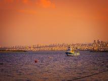På en kall vårdag finns det en fiskebåt från Blacket Sea och en sikt av den Samsun staden royaltyfri fotografi