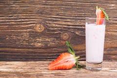 På en mörk träbakgrund, en yoghurt och skivade nya jordgubbar royaltyfri foto