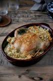 På en maträtt, en bakad höna med ris och grönsaker arkivbild
