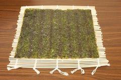 På en matt bambu, täcker Nori för sushi Royaltyfri Bild