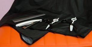 På en orange stol en uppsättning av objekt, sax och hårkammar, för klippande valos Arkivfoton