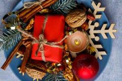 På en platta är en liten gåvaask, en brinnande stearinljus, valnötter och kanelbruna pinnar Royaltyfria Bilder