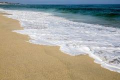 På en strand vid vattnet av havet Royaltyfri Bild