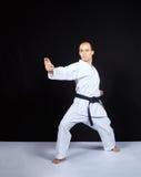 På en svart bakgrund utbildar en idrottsman nen i karategi ett kvarter med hans hand Royaltyfri Foto