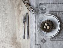 På en tabell en servett med en platta en gaffelkniv som ett rede med ett ägg av en pil fattar Arkivfoto