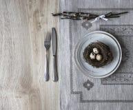 På en tabell en servett med en platta en gaffelkniv som ett rede med ett ägg av en pil fattar Royaltyfri Foto