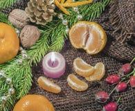 På en tabell som täckas med säckväv, är stearinljus är tangerin, kottar, gran eller sörjer fattar och bär härlig vektor för julde Arkivbilder
