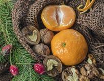 På en tabell som täckas med säckväv, är stearinljus är tangerin, kottar, gran eller sörjer fattar och bär härlig vektor för julde Arkivfoto