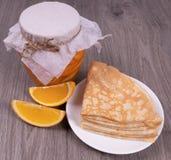 På en texturerad träbakgrund är en krus av orange sirap bredvid den en platta av pannkakor och skivade skivor för ‹för †oran arkivbild