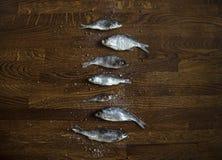 På en träbakgrund av små delfin för mörk brunt i mittlögner saltar en stor den vertikala raden saltad torkad fisk pepparkoriander arkivfoto