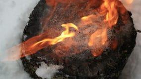 Is på en trästubbe smälter under en ström av brand i ultrarapid stock video