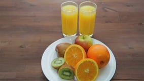 På en trätabell är en platta av frukt och två exponeringsglas av orange fruktsaft lager videofilmer