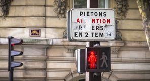 På en tricolor trafikljus indikerar ett tecken i franskt till gångare för att korsa itu etapper royaltyfri fotografi