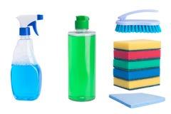 På en vit bakgrund flaskor för rengörande yttersidor, en borste, trasor, mång--färgade svampar arkivbild