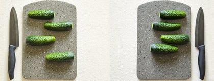 På en vit bakgrund ligger fyra gurkor på ett stenbräde, en kniv lokaliseras bredvid den royaltyfria bilder