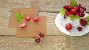 På en vit platta, som ligger på en ljus trätabell, är en jordgubbe och en körsbär Kameraflyttningarna på dockan stock video