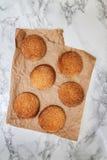 På en vit tabell för marmor sandiga runda kakor, en som är bruten, överkant VI Arkivfoton
