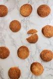 På en vit tabell för marmor sandiga runda kakor, en som är bruten, överkant VI Royaltyfria Bilder