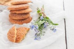 På en vit tabell, sandiga runda kakor, den som är bruten, och en bukett Royaltyfria Foton