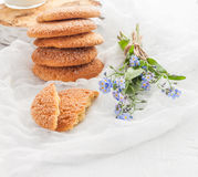 På en vit tabell, sandiga runda kakor, den som är bruten, och en bukett Royaltyfri Fotografi