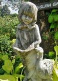 På engelska trädgård för flickaskulptur Arkivfoto