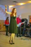 På etapp pop-vaggar musikerna gruppgrönmyntan och sångaren Anna Malysheva Rött Röd hövdad Glam vaggar att sjunga för flicka Royaltyfri Fotografi