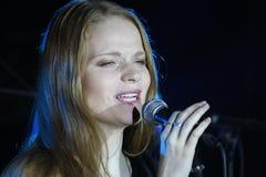 På etapp pop-vaggar musikerna gruppgrönmyntan och sångaren Anna Malysheva Rött Röd hövdad Glam vaggar att sjunga för flicka Royaltyfri Foto