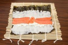 På ett bambuMat Nori blad med ris ost, lax Royaltyfria Bilder