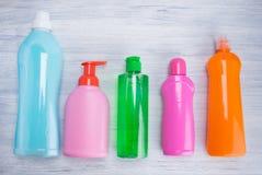 På ett ljust - grå bakgrund, mång--färgade flaskor med flytande för rengörande yttersidor, ordnade i rad arkivfoto