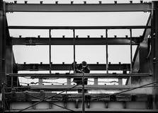På ett svartvitt foto av byggmästaren på arbete som tar bort damm från metallramen royaltyfri foto