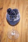 Wineexponeringsglas med björnbär in mig Royaltyfri Foto