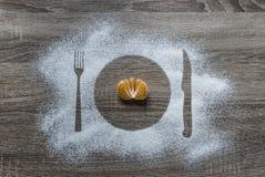 På ett träbakgrundsmjölpulver pudrad mandarin för lögner för anordningar för kniv för gaffel för platta för snökonturplatta halv  Arkivbild