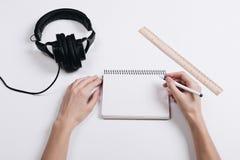 På ett vitt skrivbord är hörlurar, en linjal och en anteckningsbok, kvinnligH royaltyfri foto