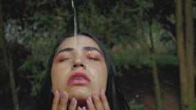 På framsidan av en härlig brunettflicka med makeup häller vatten från över droppar av vatten på kroppen av en flicka 4K video 4K arkivfilmer