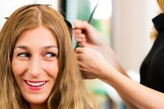 På frisören - kvinnan får ny hårfärg Arkivfoton